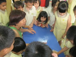 Aunty Helen demonstrates how to wipe the table clean and free from germs using a washcloth.