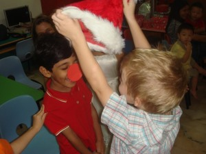 Lukas passes the hat to Manan during the Rudolph the Red Nosed Reindeer Relay.