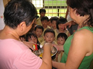 Aunty Goh (left) and Aunty Helen (right) demonstrates how to beat an egg to the children.