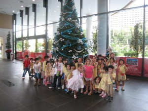 Children posing in front of the giant Christmas Tree at Kids Amaze.