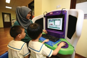 Teacher working with children in an interactive program at KidSmart console provided by IBM.