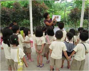 The tour guide explaining to the children where chocolates come from while showing them a picture of the cocoa fruit.